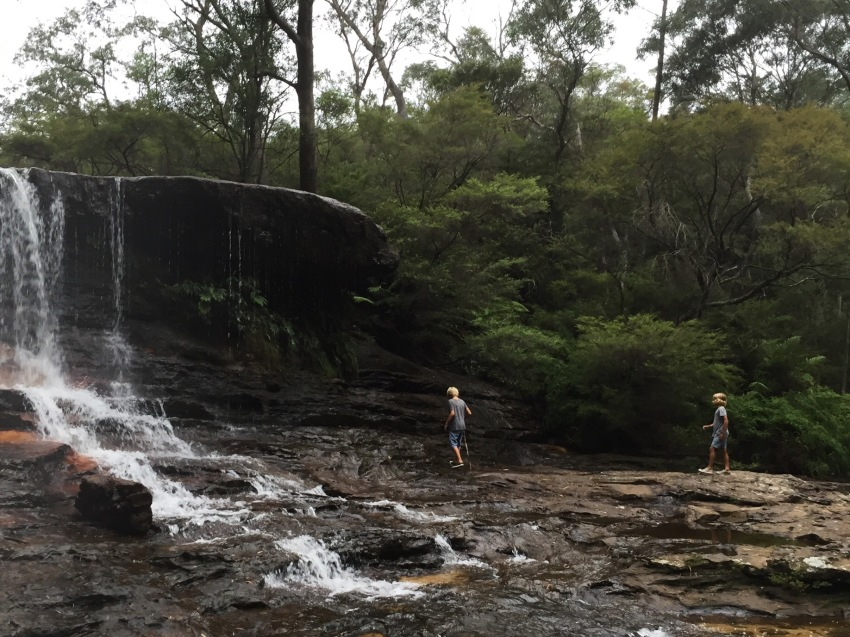 Boys walking in waterfall